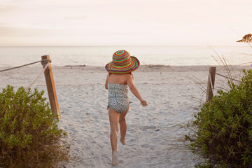 A cute little girl running towards the beach in a big straw hat