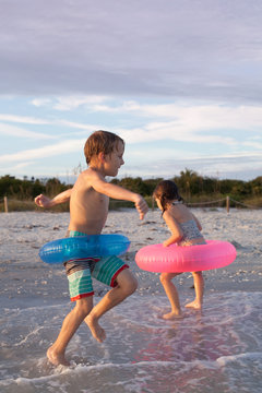 A young boy and girl playing in the water at the beach with pink and blue rafts