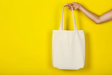 Female hand holding white cotton eco bag on yellow background