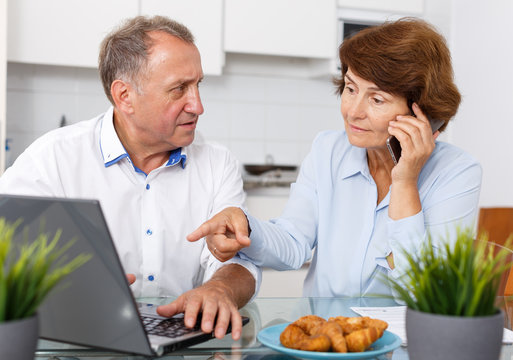 Smiling mature family couple with phone using laptop at kitchen table