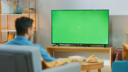 Happy Guy Sitting At Home in the Living Room on His Chair, Watching Green Chroma Key Screen,...
