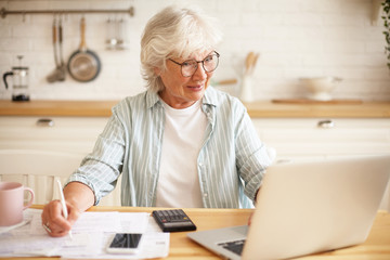 Positive elderly female having joyful look, managing family budget at kitchen table, sitting in front of open laptop, writing down using pencil. Senior woman paying domestic bills via website