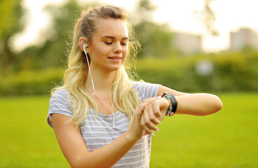 Young athlete listening to music during workout at park and setting the smart watch - Young woman adjusting the smartwatch before sport activity in the morning.