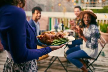 Group of diverse friends having dinner al fresco in urban setting