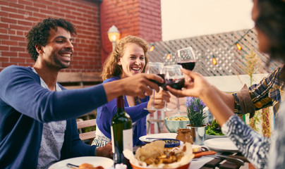 Group of diverse friends having dinner and a glass of wine al fresco in urban setting