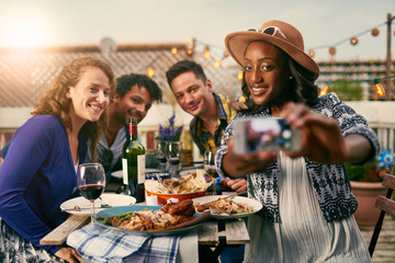 Group of diverse friends taking selfies pictures having dinner al fresco in urban setting