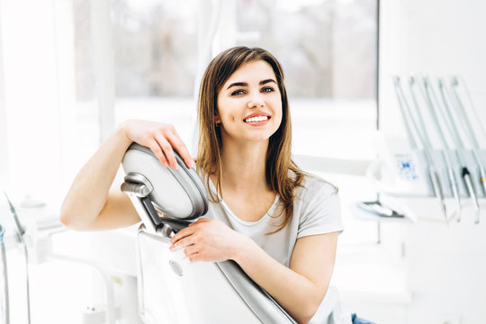 Pretty happy and smiling dental patient sitting in the dental chair at the dental office.