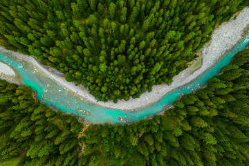Aluminium Prints Forest river Inn River flowing in the forest in Switzerland. Aerial view from drone on a blue river in the mountains