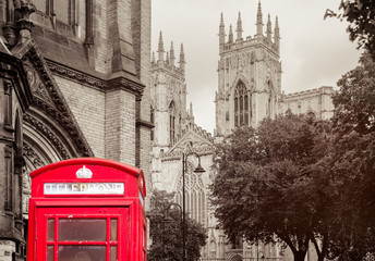 Old british red phone booth with the York Cathedral -  Background toned in sepia
