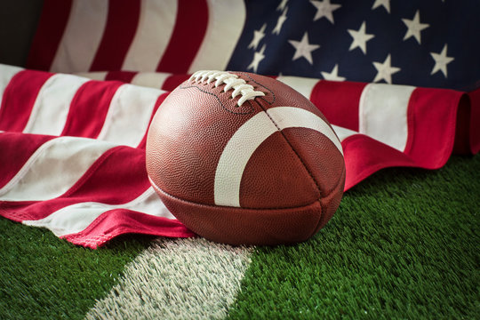 Football on field with stripe and American flag behind