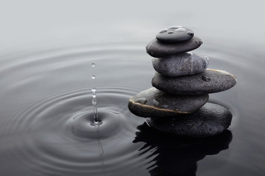 Zen stones in balanced pile in water on rippled water surface and water drop.