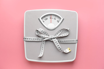 Scales and measuring tape on color background. Weight loss concept