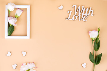 Empty white frame with flowers eustoma and Love words on beige paper background with copy space. Holiday concept