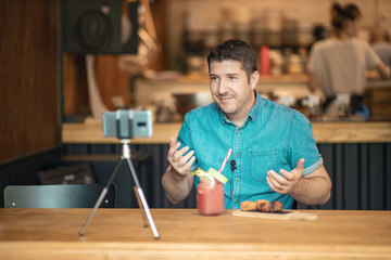 Food blogger streaming live on social media - Man creating blog video content using smart phone camera on tripod in his small restaurant