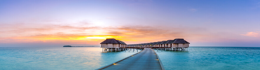 Foto auf Leinwand Strand Amazing sunset panorama at Maldives. Luxury resort villas seascape with soft led lights under colorful sky. Beautiful twilight sky and colorful clouds. Beautiful beach background for vacation holiday
