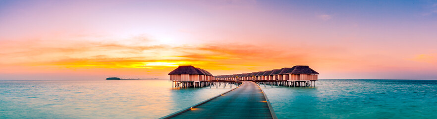 Fotobehang Oranje Amazing sunset panorama at Maldives. Luxury resort villas seascape with soft led lights under colorful sky. Beautiful twilight sky and colorful clouds. Beautiful beach background for vacation holiday