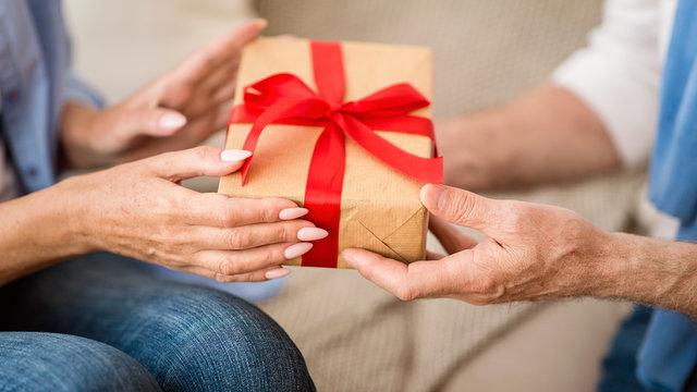 Senior woman giving Christmas gift box to elderly man