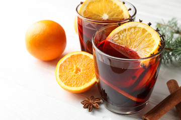 Photo sur Aluminium The Glasses of tasty mulled wine with orange on white wooden background, close up