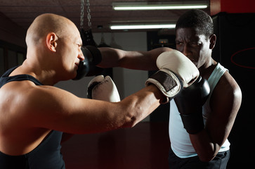 Two athlete men in sportswear exercising boxing sparring in the hall
