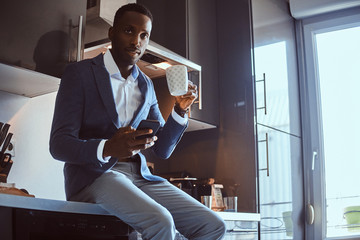 Groomed african businessman is enjoying his morning coffee while chatting by mobile phone at his kitchen.