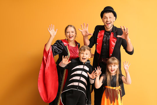 Family in Halloween costumes on color background