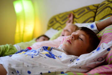 The boy stretches after a deep sleep. A school-age boy wakes up Saturday morning after a work week. Healthy sleep conch for children.
