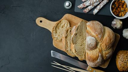 Fototapeta Pyszny chrupiący chleb z salami, orzechami, czosnkiem i oliwą. Widok z góry. obraz
