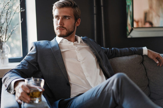 Handsome and successful businessman in stylish suit holding glass whiskey while sitting at office.