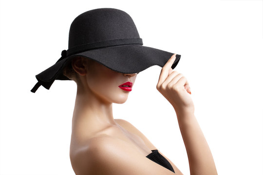 girl in a black hat posing in the Studio. red lips. the hat covers part of the face