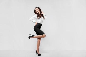Portrait of young modern business woman. Smiling beautiful slim brunette with curly hair female business leader in smart casual wear expressing happy emotions. Gray background. Career success concept.