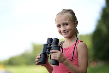 Petite fille regardant à travers des jumelles en plein air