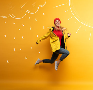 Girl with jacket jumps to the sun from the rainy weather. Joyful expression. Yellow background