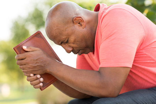 African American man praying and reading the Bible.