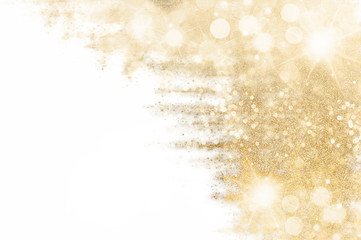 Festive shiny sparkles and twinkling bokeh. Golden glittering background.