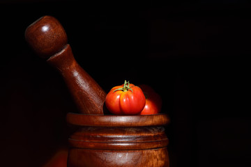 Close-up of a wooden mortar and pestle with tomatoes in a mortar being processed into sauce, against a dark background with text box