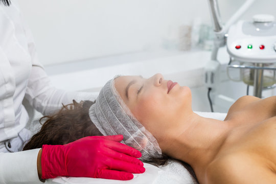 Beautiful woman relaxing during a facial steam treatment at a beauty spa.