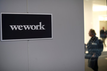 A man and woman walk inside offices run by WeWork in Philadelphia