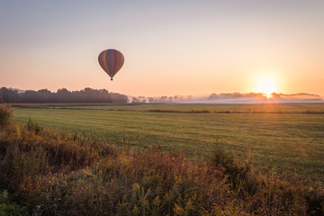 Zelfklevend Fotobehang Ballon Hot air balloon lifts off over a farm field at sunrise, Pine Island, NY, early fall