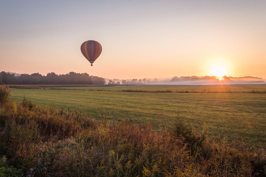 Hot air balloon lifts off over a farm field at sunrise, Pine Island, NY, early fall