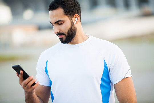 Man after working out in the city park and using his mobile phone