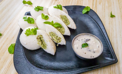 Steamed Idlis stuffed with chicken minced with mint leaves along with white coconut chutney in a black plate