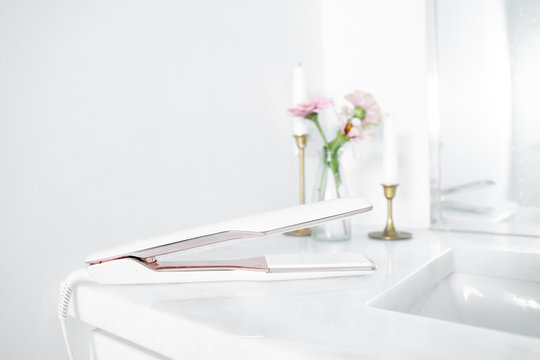 Modern hair straightener on white marble countertop, brass decor with candles and flowers, bobby pins, girly bathroom, copy space
