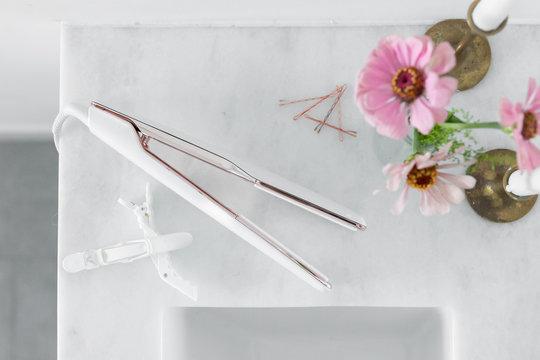 Top view of hair straightener on marble bathroom countertop