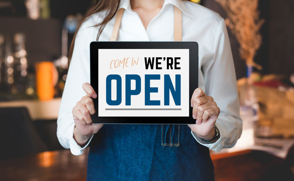 woman barista wear jean apron holding come in we are open sign on tablet to customer at bar counter with smile emotion,Cafe restaurant service concept,Owner of start up small business.