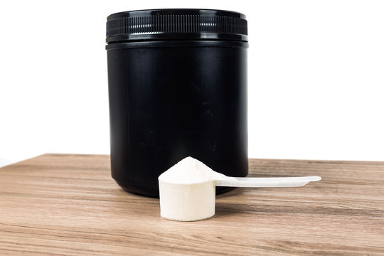 Black supplement tub with scoop on a wood patterned background