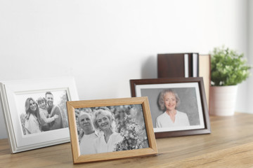Framed photos on cabinet near white wall