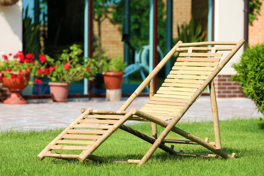Wooden deck chair in beautiful garden on sunny day