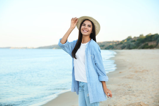 Beautiful young woman in casual outfit on beach
