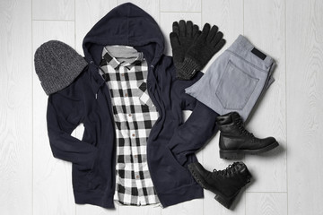 Fototapete - Flat lay composition with winter clothes and boots on white wooden background