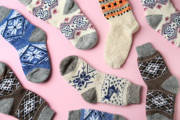 Different knitted socks on pink background, flat lay. Winter clothes